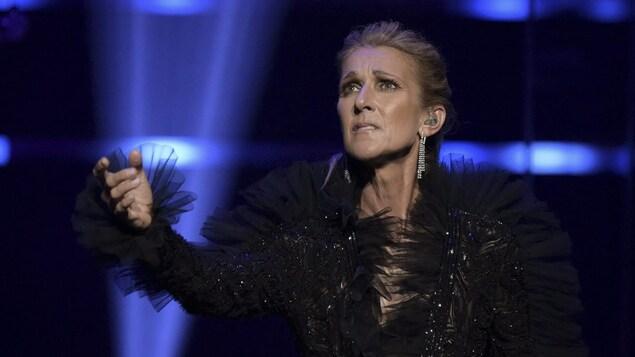 La chanteuse vêtue d'une robe noire lève la main vers le ciel alors qu'elle est sur scène.