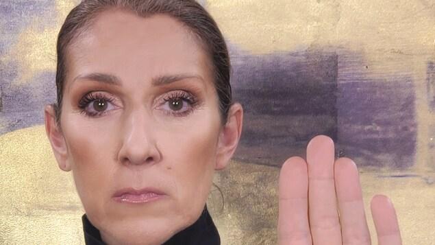 Céline Dion regarde la caméra, le visage sérieux. Elle lève sa main pour montrer le « D » qui y est inscrit.
