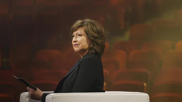 Céline Galipeau assise dans un théâtre.