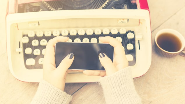 Des mains féminines tiennent un cellulaire au-dessus d'une vieille machine à écrire