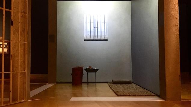 Reproduction de la cellule de prison de Mandela. Dans la cellule, on voit un tapis au sol, une petite table et une poubelle qui servait à Mandela de toilette.