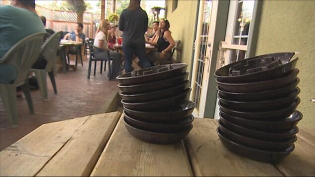 Des cendriers empilés sur une table d'une terrasse.