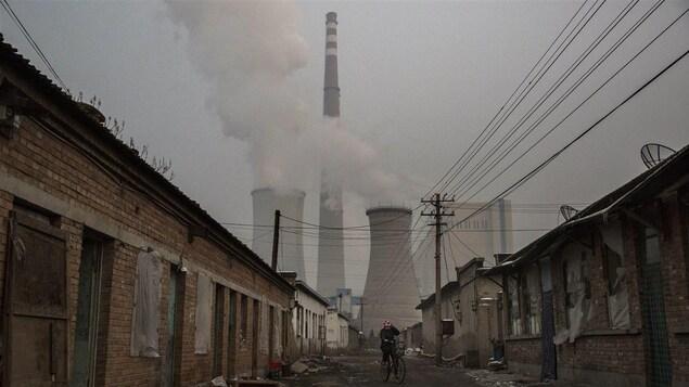 Un homme roule à vélo dans une rue désaffectée déserte avec en arrière-plan la cheminée d'une centrale électrique qui fume.