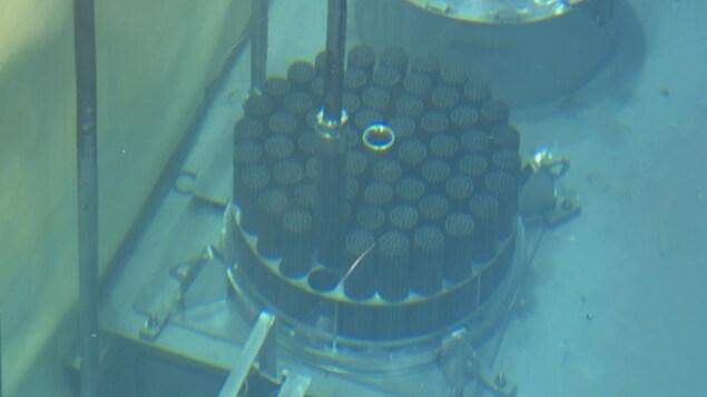 Des grappes de combustible immergées sont manipulées par un bras robotisé.