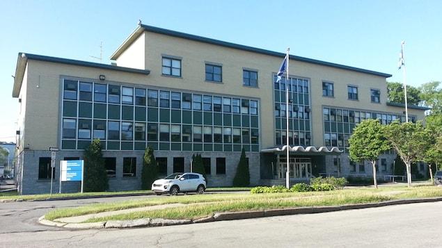 Vue sur la façade du bâtiment abritant la Cour municipale de Québec et le poste de police de l'arrondissement de La Cité-Limoilou. Il s'agit d'une construction en briques jaunes de trois étages.