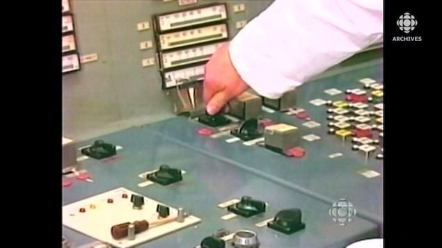 Un homme en blouse blanche tourne une clé sur un moniteur de la centrale de Tchernobyl.