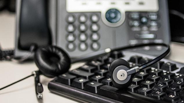 Un casque d'écoute pour téléphone repose sur un clavier d'ordinateur. À l'arrière-plan, on aperçoit un téléphone à touches.