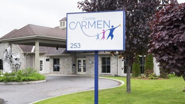 """Affiche sur laquelle on peut lire """"Centre CARMEN"""" devant un édifice."""