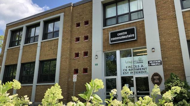 Façade du centre communautaire de Louiseville, avec une pancarte bien en vue dans la porte indiquant que l'accès y est interdit.