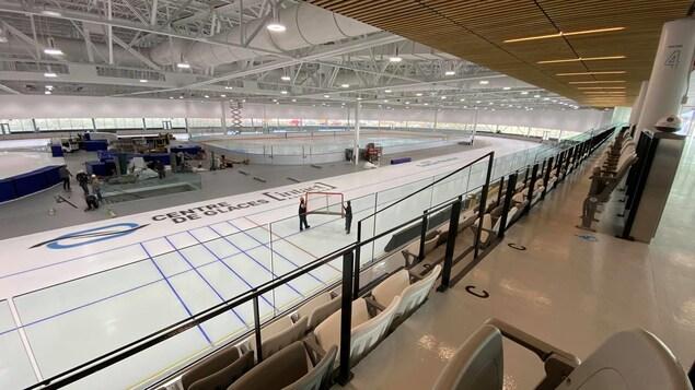 Deux employés traverse l'anneau de glace avec un filet de hockey.