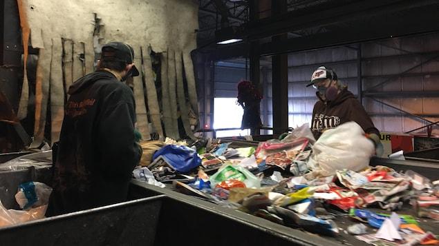 Des employés se tiennent chaque côté d'un convoyeur pour trier les objets qui s'y retrouvent.