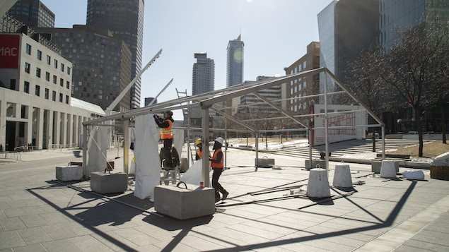 Des travailleurs installent une tente.