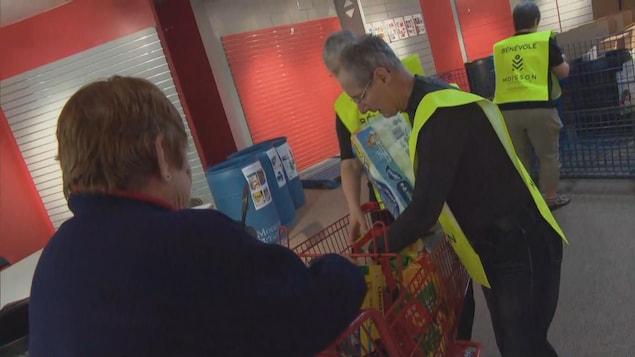Des bénévoles recueillent des dons.