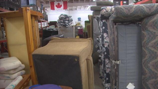 Une salle bondée de canapés de chaises et d'étagères.