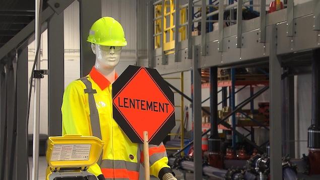 Un mannequin tient un panneau de circulation.