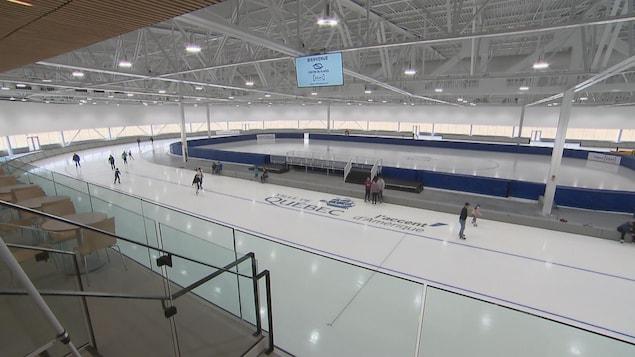 Vue sur une large piste de patinage de vitesse flambant neuve. Des patineurs glissent dessus.