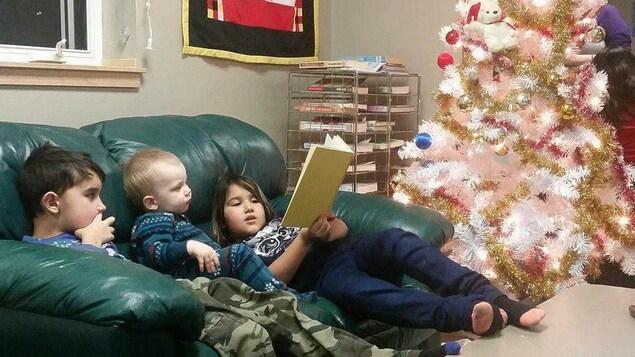 Trois enfants lisent un livre sur un divan.