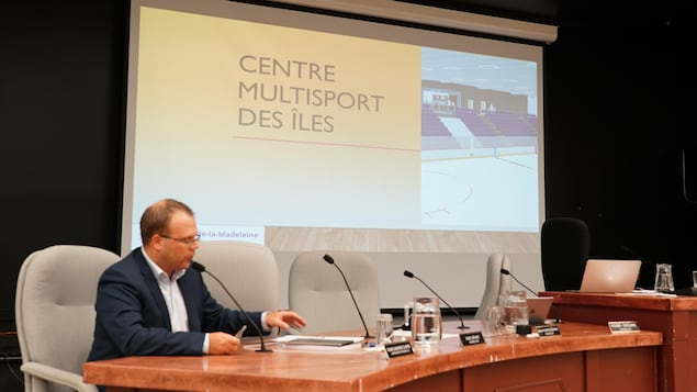 """Le Maire est assi à une table devant un écran projecteur où il est écrit : """"Centre multisport des Îles"""""""