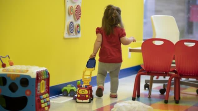 Une petite fille marche en traînant un petit camion dans une garderie.