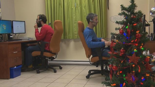 Deux intervenants répondent aux appels avec des casques d'écoute.