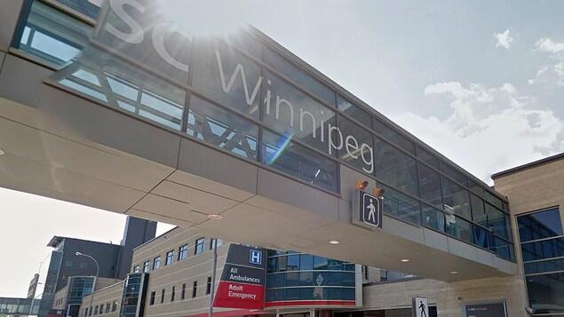 Une passerelle majoritairement en verre qui se connecte au deuxième étage d'un édifice hospitalier