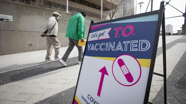 Un homme qui en accompagne un autre plus âgé passe devant l'enseigne qui indique comment se rendre au centre de vaccination.