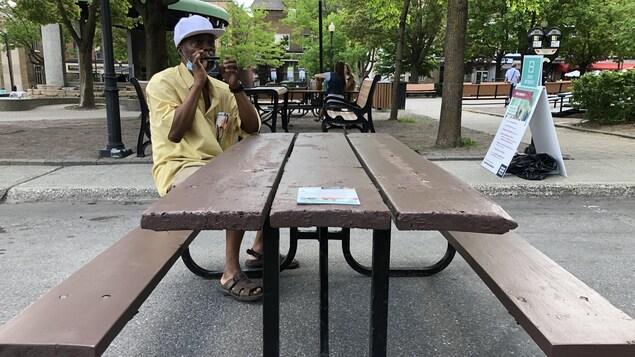 Un homme est assis à une talble à pique-nique.