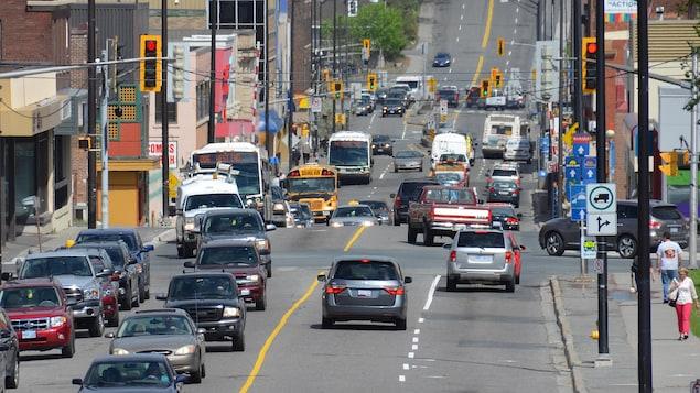Des véhicules à la file sur une artère achalandée. Il y a des autobus, des camionnettes, des voiture et un taxi.