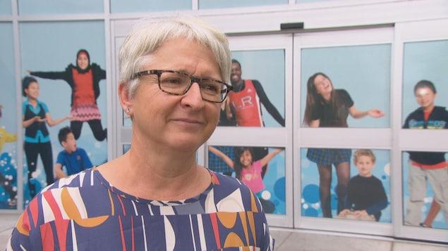 Édith Dumont répond aux questions d'un journaliste à l'extérieur d'un immeuble.