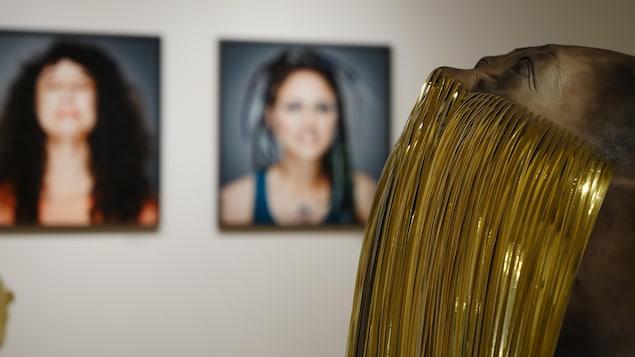 Une sculpture en céramique d'un visage avec la bouche cachée par des longs fils de céramique. Dans l'arrière-plan on y trouve deux portraits de femme.