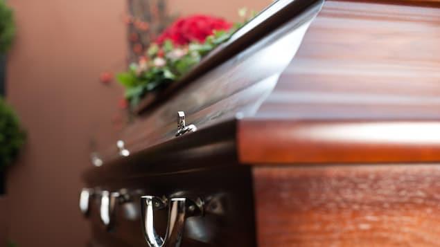 Un cercueil au cours d'une cérémonie funéraire avec des fleurs posées dessus