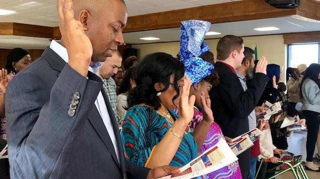 Un homme plaide sous serment avec sa main droite levée et les yeux fermés lors d'une cérémonie de citoyenneté bilingue.