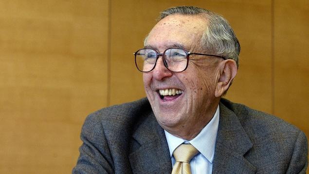 De profil, un homme portant des lunettes sourit à pleines dents.