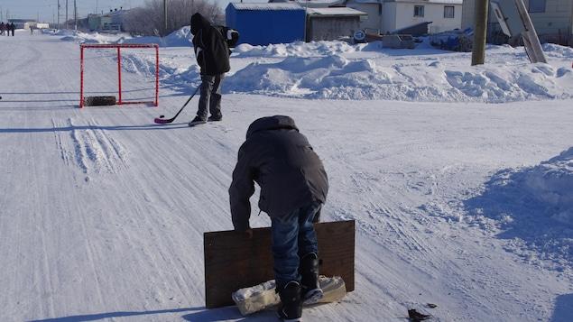 Un des enfants avec un bâton de hockey et une rondelle se dirige vers le but.