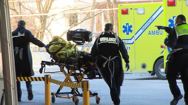 Des ambulanciers transportent un patient sur une civière.