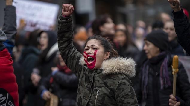 Une manifestante a le visage recouvert d'une marque représentant une main rouge.