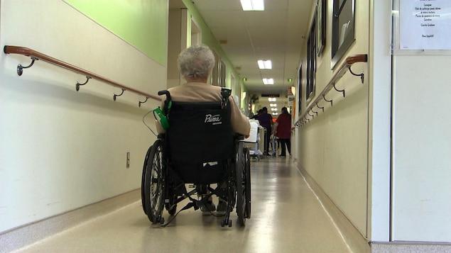 Une femme se déplace dans un couloir en chaise roulante.