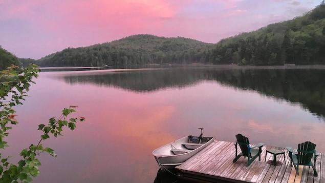 Un lac à la tombée du jour, avec un quai en bois, des chaises et une embarcation; au premier plan, le feuillage d'un arbre.