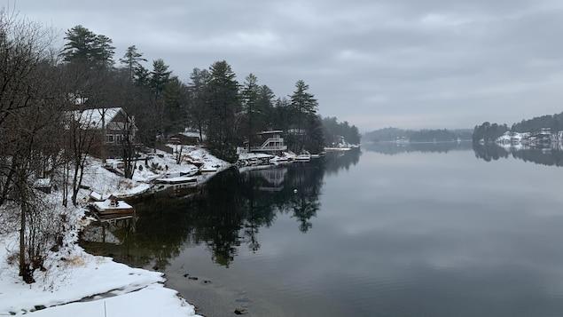 Des chalets et des quais enneigés au bord d'un lac.
