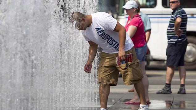Un homme se met la tête dans l'eau d'une fontaine pour se rafraîchir.