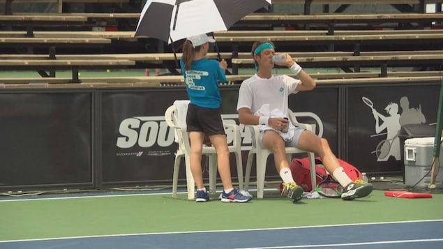 Un joueur de tennis assis boit une bouteille d'eau.