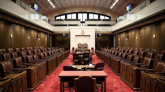 Une immense salle avec des meubles bruns et un tapis rouge.