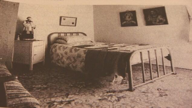 Une photo en noir et blanc sur laquelle on peut voir un lit et une statue.