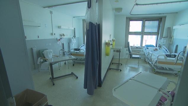 Un homme est couché dans un lit d'hôpital. L'autre lit est vide.