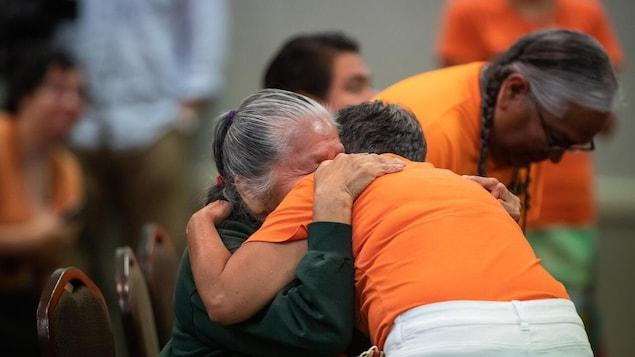 Une femme autochtone âgée pleure et un individu portant un chandail orange la console.