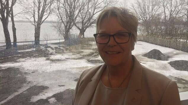 La mairesse de l'arrondissement de Rivière-des-Prairies-Pointe-aux-Trembles, Chantal Rouleau, devant une fenêtre permettant de voir le fleuve
