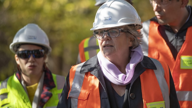 Deux femmes et deux hommes vêtus de vestes orangé et de casques de protection sur un chantier.