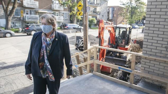 Chantal Rouleau, portant un masque, dehors à l'entrée d'une école avec, derrière elle, une tractopelle.