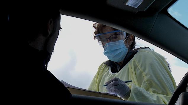 L'infirmière pose des questions à un automobiliste.