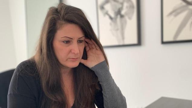 Chantale Renaud, assise à sa table de cuisine, regarde l'écran de son ordinateur portable et a les doigts de la main gauche posés sur sa tempe.